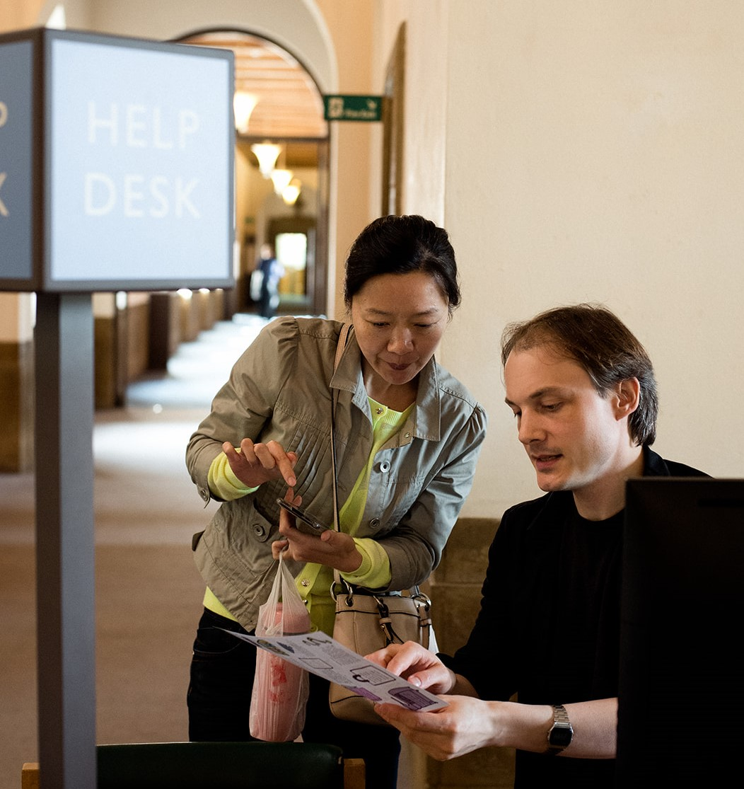 Librarian providing assistance to library user by pointing to written information in a leaflet