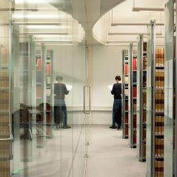 Person reading journal in corridor of bookshelves